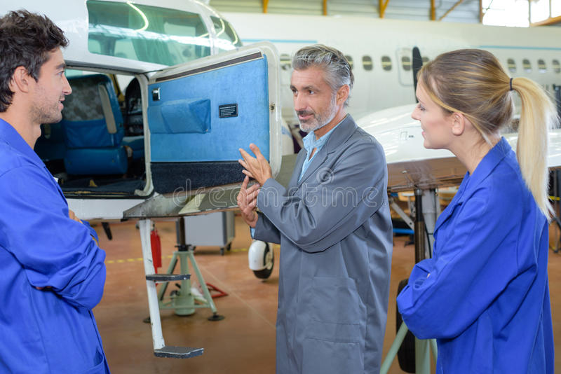Students looking in compartment aircraft stock photos