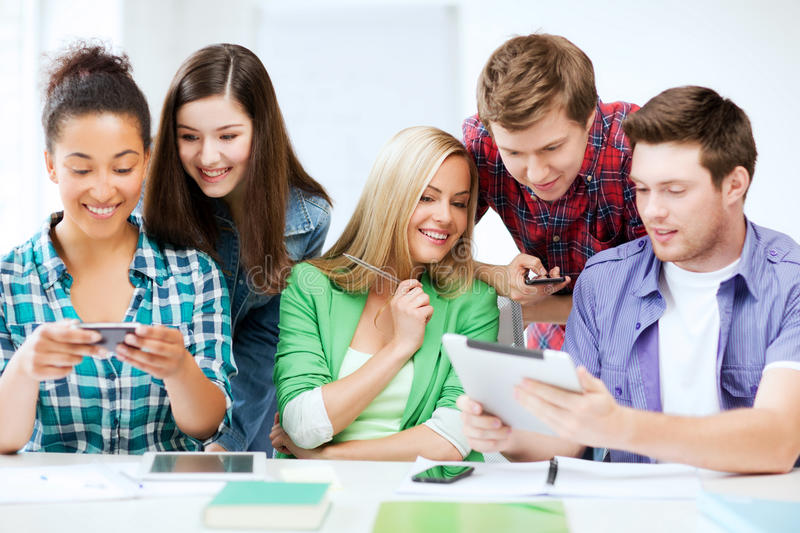 Students looking at smartphones and tablet pc stock images