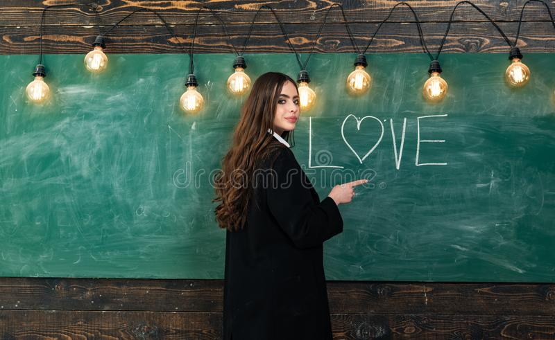Students love. Portrait of girl teenager in love. Young cute teenage girl in classroom at blackboard. Young attractive stock image