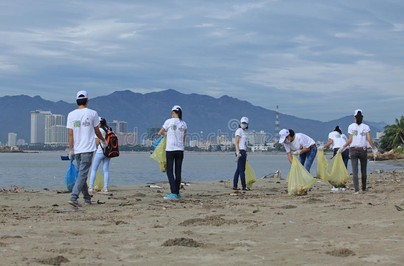 Students of Nha Trang University cleaning the beach. NHA TRANG, VIETNAM - JUNE 16, 2013: Students of Nha Trang University cleaning the beach within a volunteer stock photo