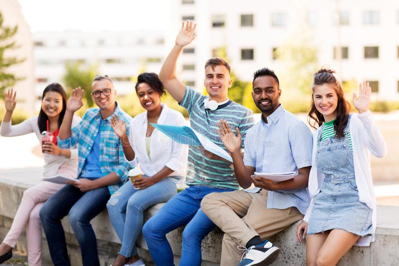 Students with notebook waving hands outdoors. Education, international and people concept - group of happy exchange students with notebook and takeaway drinks royalty free stock photo