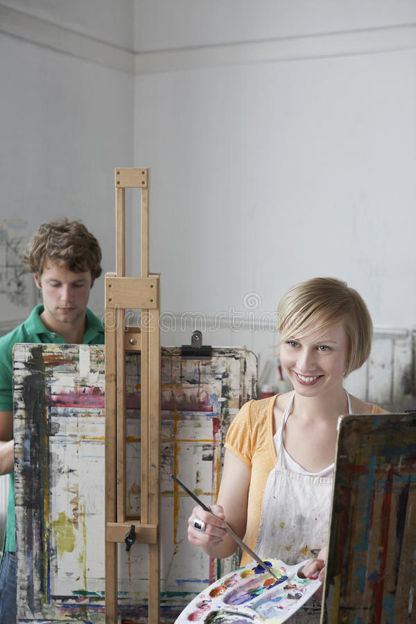 Students Painting At Easels In Art Class. Young male and female students painting at easels in art class stock photography