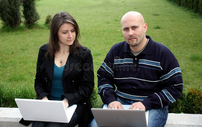 Students in a park. Two students studyng using laptops working in a park royalty free stock photo