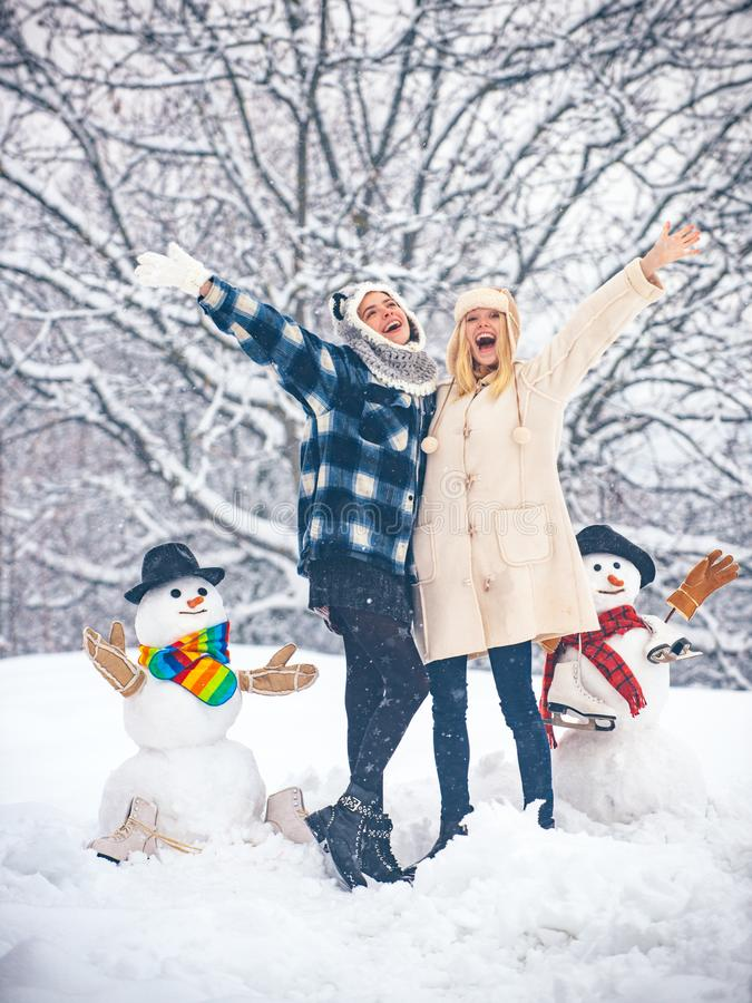 Students party and Christmas celebration. Happy girl playing with a snowman on a snowy winter walk. Christmas Girl and stock photography