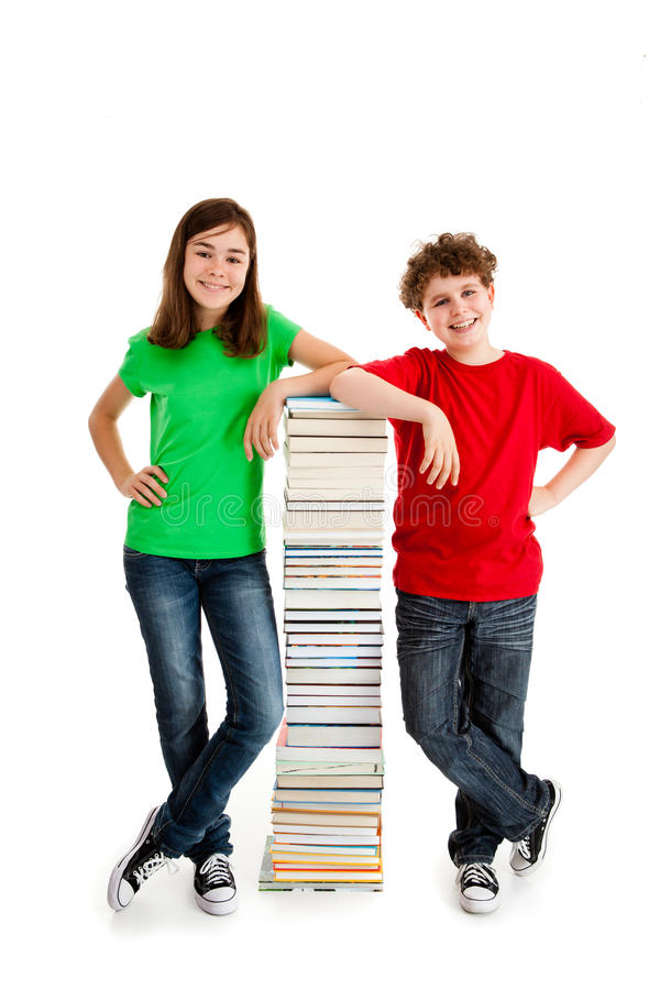 Students and pile of books. Students standing nex to a pile of books royalty free stock photography