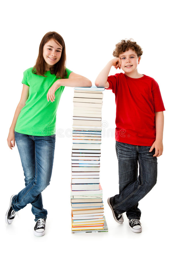 Students and pile of books. Students standing nex to a pile of books royalty free stock images