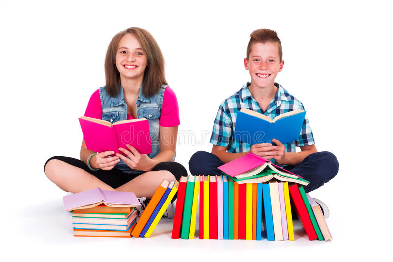 Students reading books. Teenage friends with many books in front on them smiling and reading stock photography