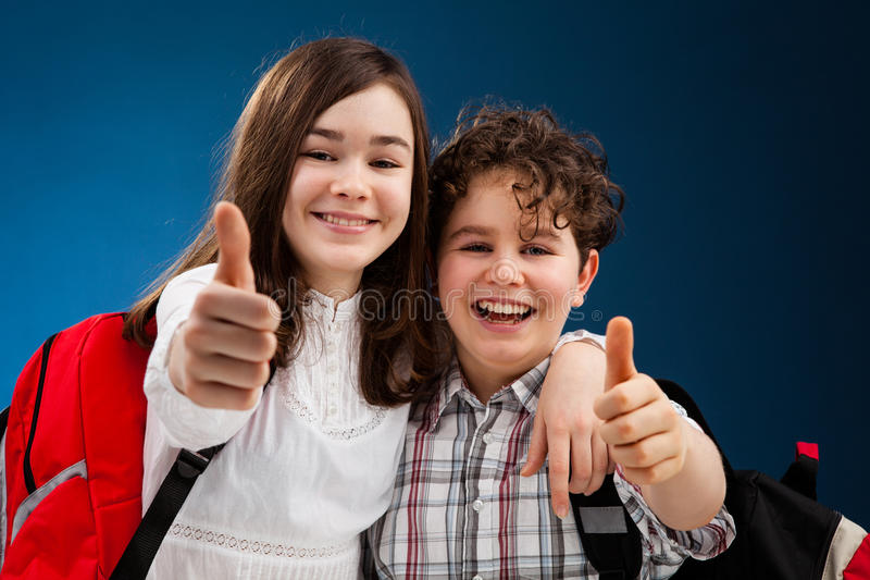 Students showing Ok sign. Happy young kids going to school stock images