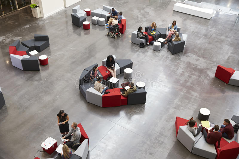 Students sit in groups in a modern university atrium royalty free stock photo