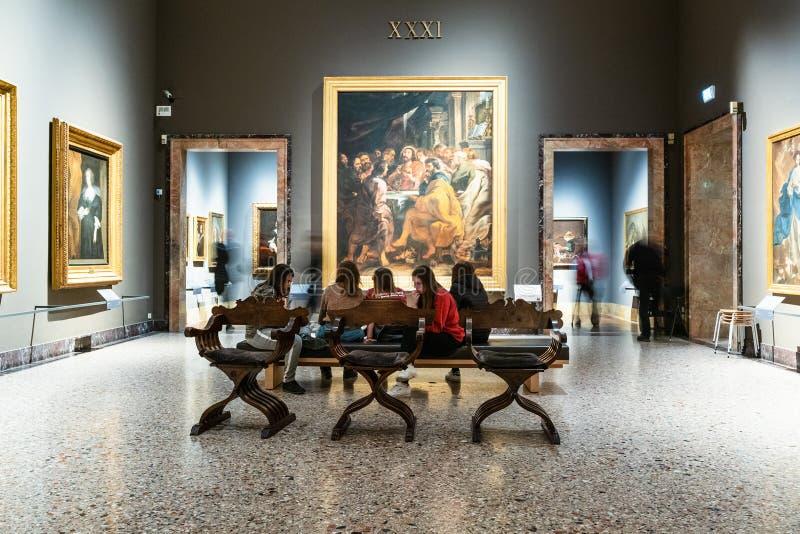 Students sit in room in Pinacoteca di Brera. MILAN, ITALY - FEBRUARY 24, 2019: students sit in room in Pinacoteca di Brera Brera Art Gallery in Milan. The Brera royalty free stock photos