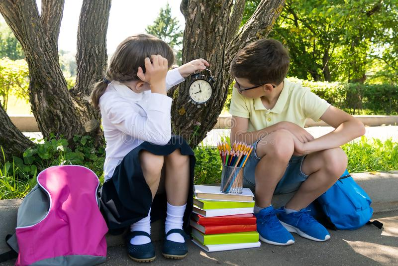 Students sit on the street with bags and books and look at the clock. Students sit on the  street with bags and books and look at the clock royalty free stock photography