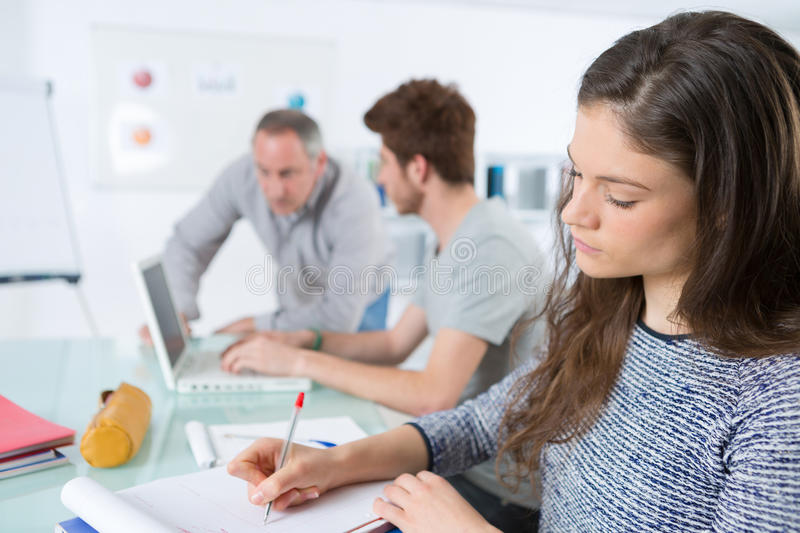 Students sitting in classroom and taking notes royalty free stock photography