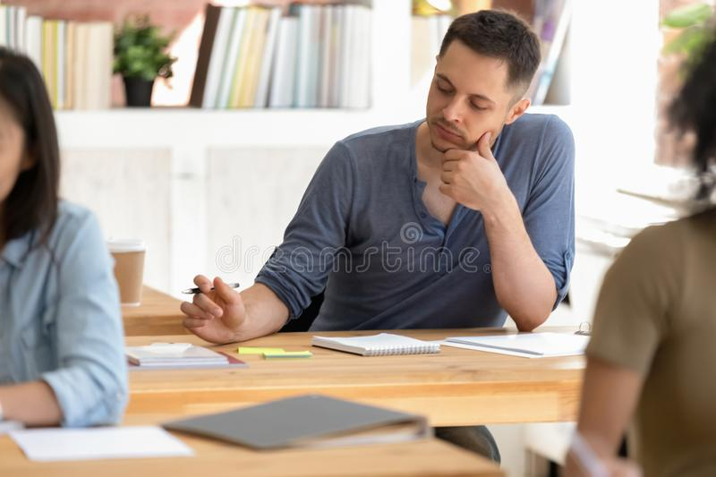 Students sitting at desks focus on caucasian guy make notes. Diverse university high school students sitting during lesson at desk in a rows focus on stock photography