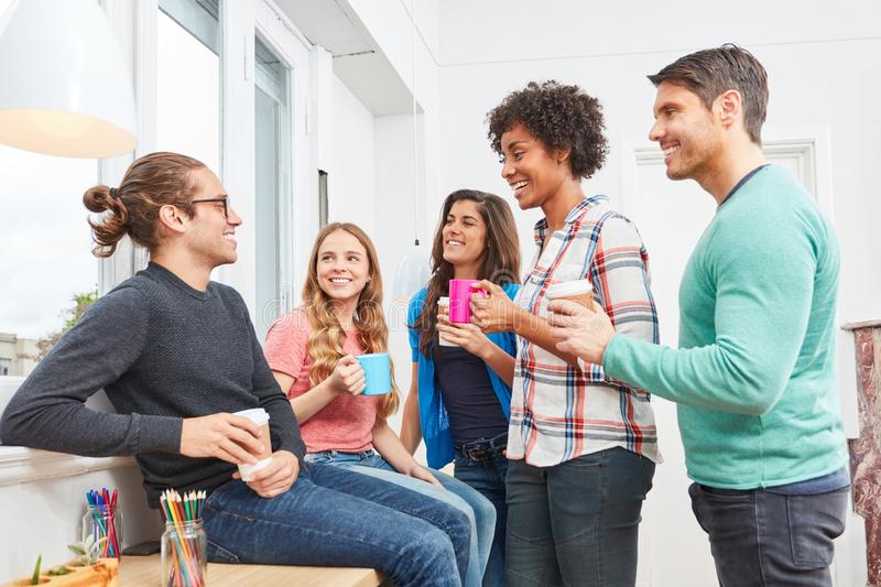 Students at the small talk in the coffee break in the office stock images