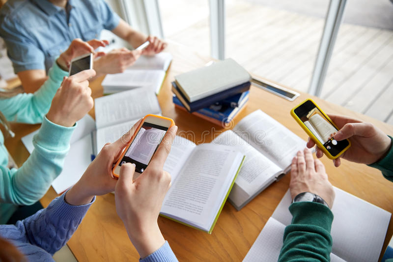 Students with smartphones making cheat sheets. People, education, technology and exam concept - close up of students with smartphones taking picture of books stock photo