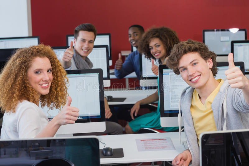 Students smiling at camera in computer class stock images
