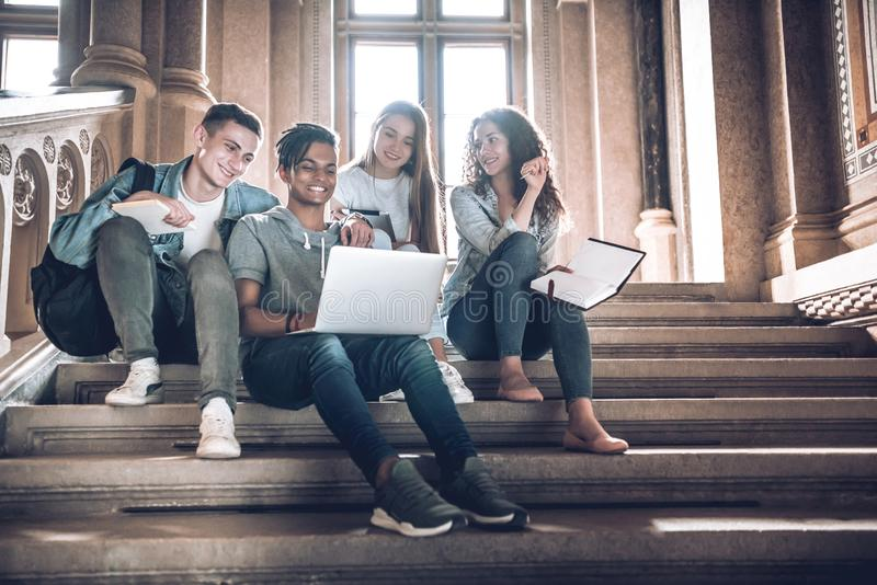 Students are spending time together.Multicultural young people using laptop while sitting on the stairs in the hall university stock image