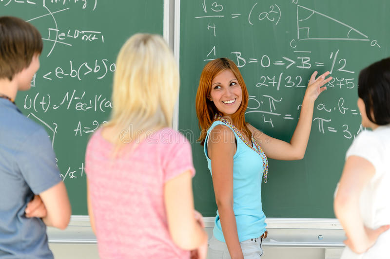 Students standing front of green chalkboard math stock photos