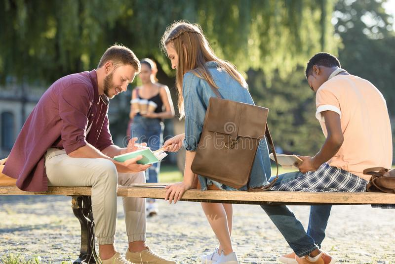 Students studying on bench in park stock image