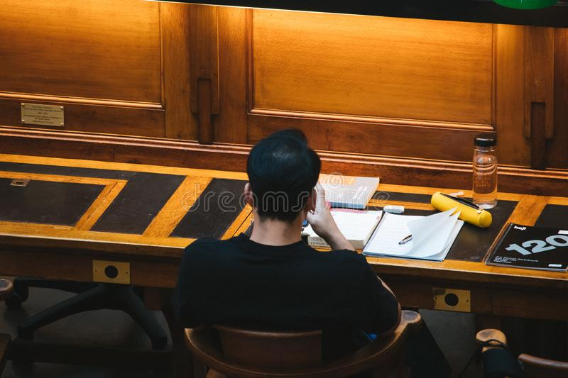 Students studying at a library using laptop computers stock photo