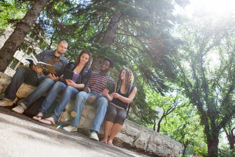 Students Studying On Parapet At University Campus Royalty Free Stock Image