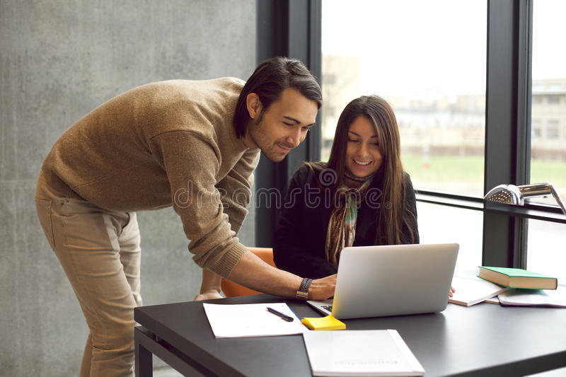 Students studying together with laptop stock photography