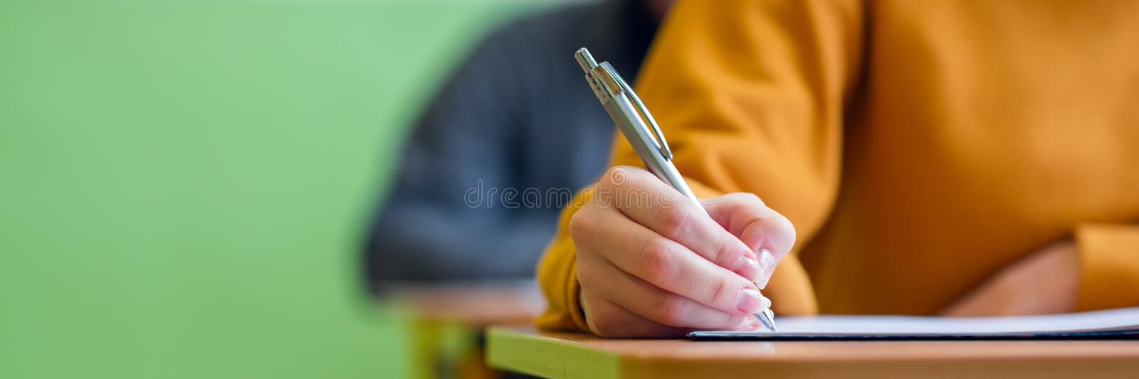 Students taking exam in classroom. Education test and literacy concept. Cropped shot, hand detail. royalty free stock photography