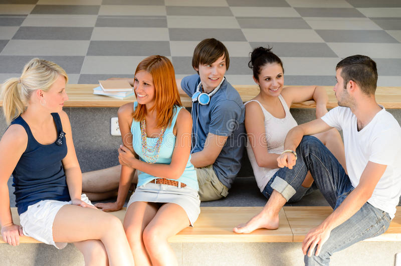 Students talking sitting on school bench royalty free stock images