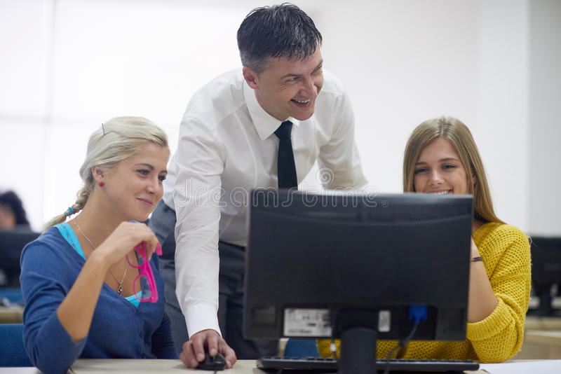 Students with teacher in computer lab classrom. Group of students with teacher in computer lab classrom learrning lessons, get help and support royalty free stock photography