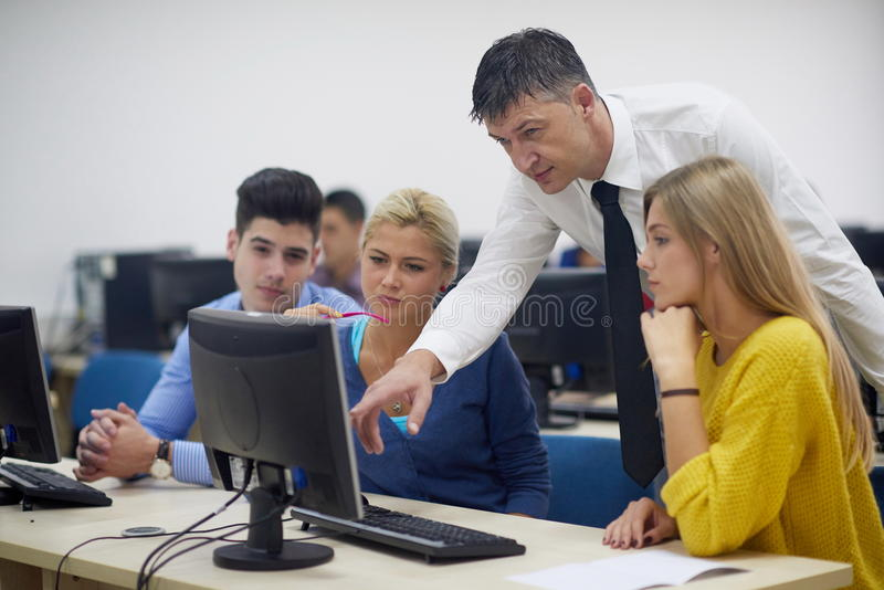 Students with teacher in computer lab classrom. Group of students with teacher in computer lab classrom learrning lessons, get help and support stock photography
