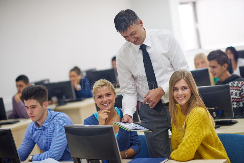 Students with teacher in computer lab classrom. Group of students with teacher in computer lab classrom learrning lessons, get help and support royalty free stock image