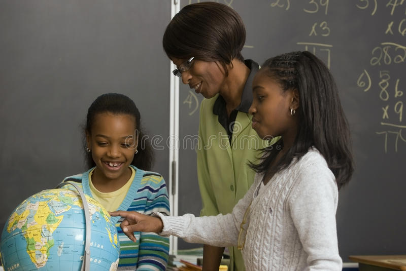 Students and teacher look at the globe stock photography