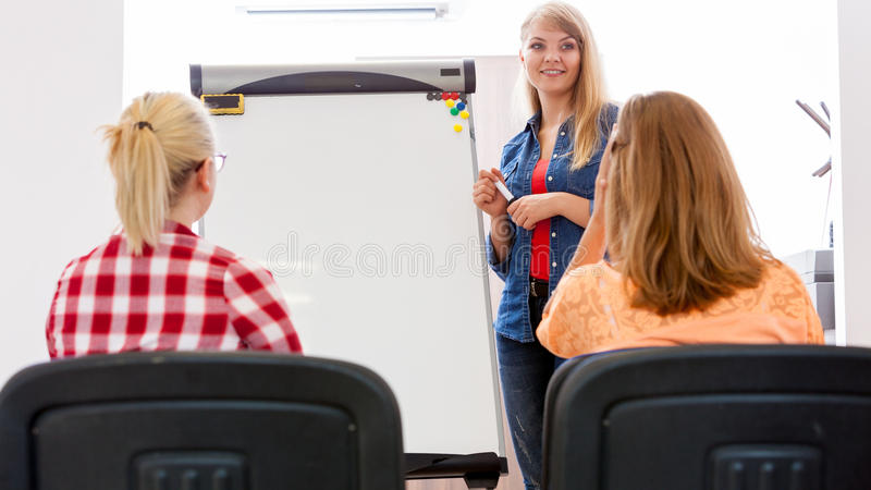 Students and teacher tutor in classroom. Teaching, studies course, meeting discussion sharing ideas concept. Woman young teacher near whiteboard and teenage stock photo