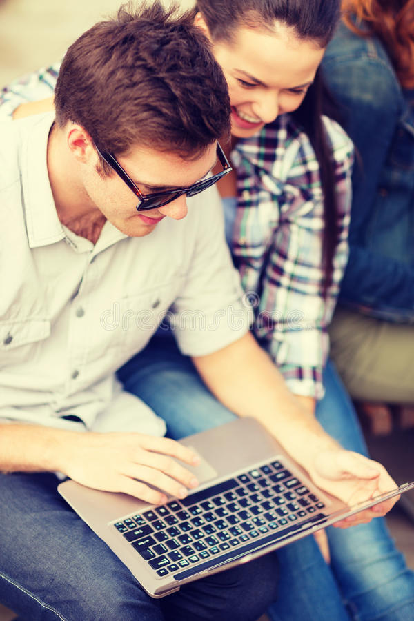 Students or teenagers with laptop computer. Summer, internet, education, campus and teenage concept - students or teenagers with laptop computer hanging out royalty free stock image