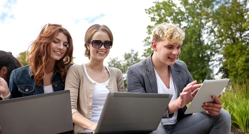 Students or teenagers with laptop computers. Summer, communication, technology , education and teenage concept - group of students or teenagers with laptop and royalty free stock images