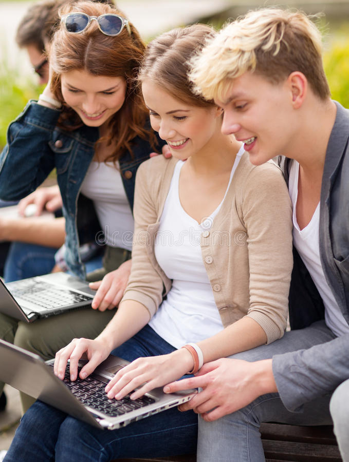 Students or teenagers with laptop computers. Summer, internet, education, campus and teenage concept - group of students or teenagers with laptop computers stock images