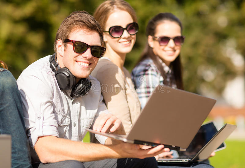 Students or teenagers with laptop computers. Summer, internet, education, campus and teenage concept - group of students or teenagers with laptop and tablet stock photo