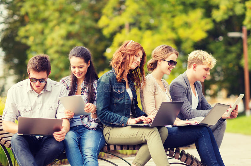 Students or teenagers with laptop computers. Summer, internet, education, campus and teenage concept - group of students or teenagers with laptop and tablet royalty free stock photography