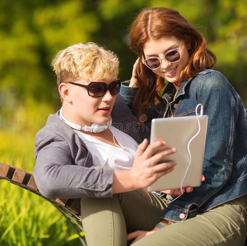 Students or teenagers with tablet pc computer. Summer, internet, education, campus and teenage concept - students or teenagers with tablet pc computer hanging stock photos