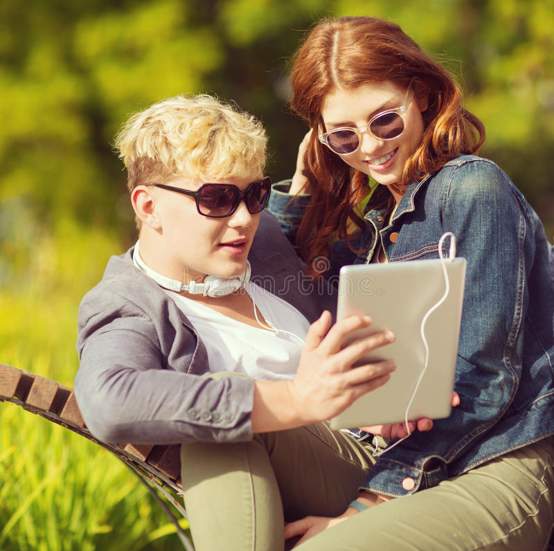 Students or teenagers with tablet pc computer. Summer, internet, education, campus and teenage concept - students or teenagers with tablet pc computer hanging royalty free stock photo