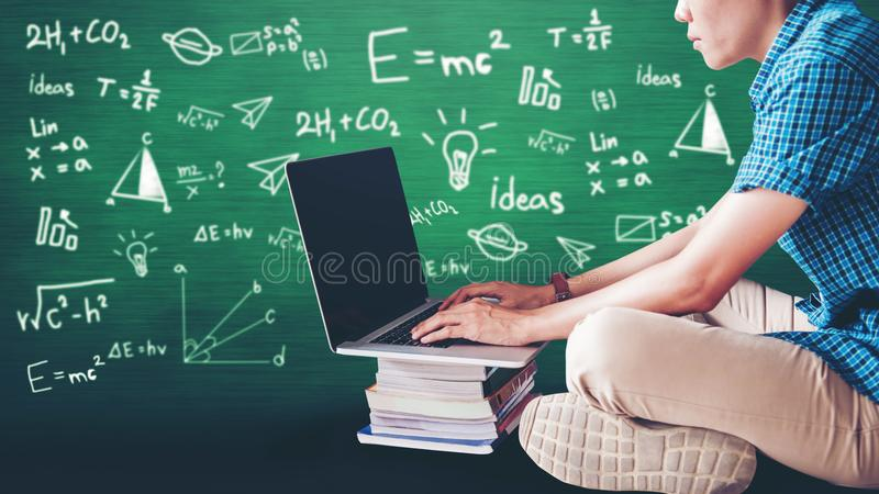 Students using laptop for research homework in college, education concept with blackboard background royalty free stock image