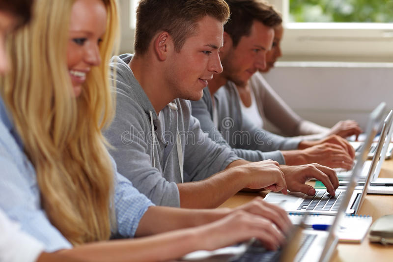 Students using laptops in class. Happy students using their laptops in university class royalty free stock image
