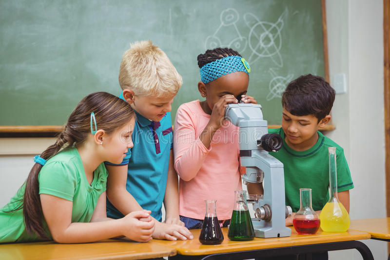 Students using science beakers and a microscope royalty free stock images