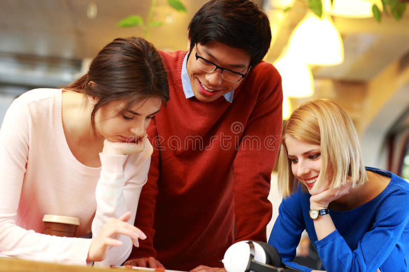 Students using tablet computer together. Happy students using tablet computer together stock photo