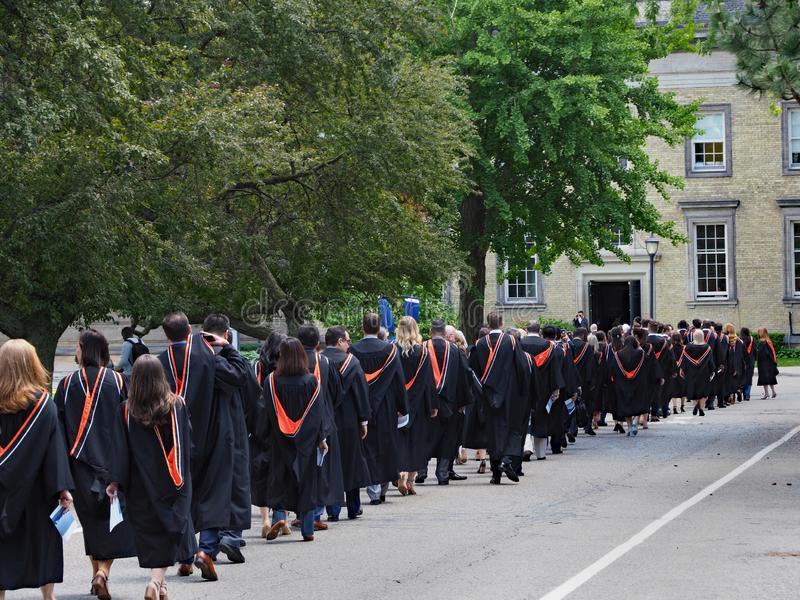 Students walking outdoors to graduation ceremony royalty free stock photo