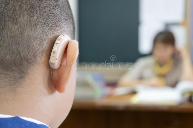 Students who wear hearing aids to increase hearing efficiency. Helps to be able to learn as much as a friend. The background is a teacher who is talking to him royalty free stock photos