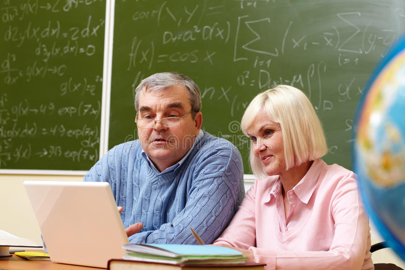 Students working. Portrait of mature men and aged female working with laptop in classroom stock image