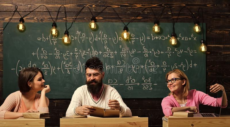 Students, young scientists . Girls, happy students looking with adoration at bearded teacher, lecturer, professor royalty free stock photography