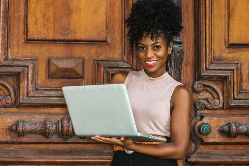 Studera för högskolestudent för lycklig ung afrikansk amerikan som kvinnligt arbetar i New York, med den afro frisyren som bär sl arkivbild