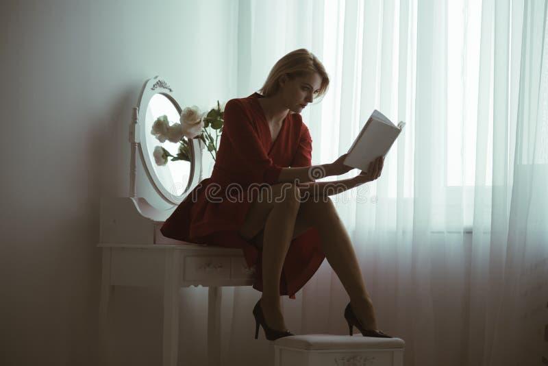 Studera poesi sexig kvinna som studerar poesisammanträde i sovrum studera hemmastadd poesi flicka i rött studera för klänning royaltyfria foton